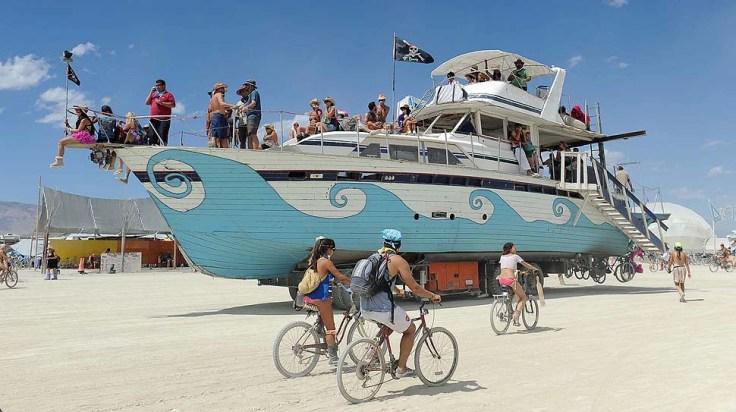 An old wooden yacht art car rolls through the playa at Burning Man on the Black Rock Desert near Gerlach, Nev. on Friday Aug. 31, 2012 on Friday Aug. 31, 2012. (AP Photo/Reno Gazette-Journal, Andy Barron)